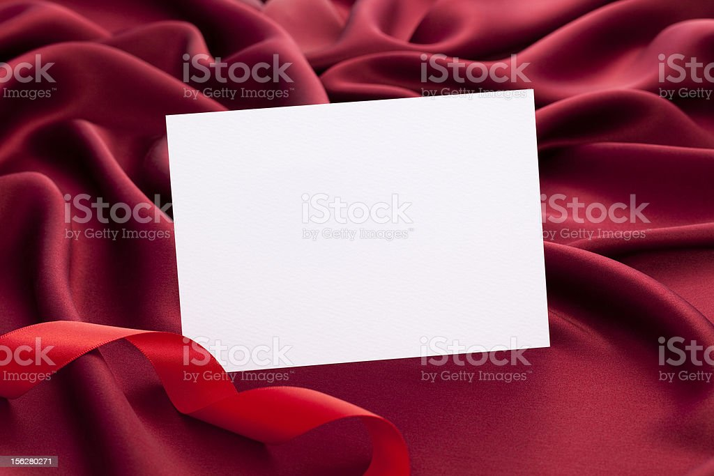 White card with space for text on red silk satin royalty-free stock photo