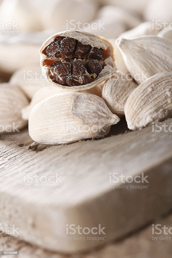 white cardamom pods on old wood, one opened macro royalty-free stock photo