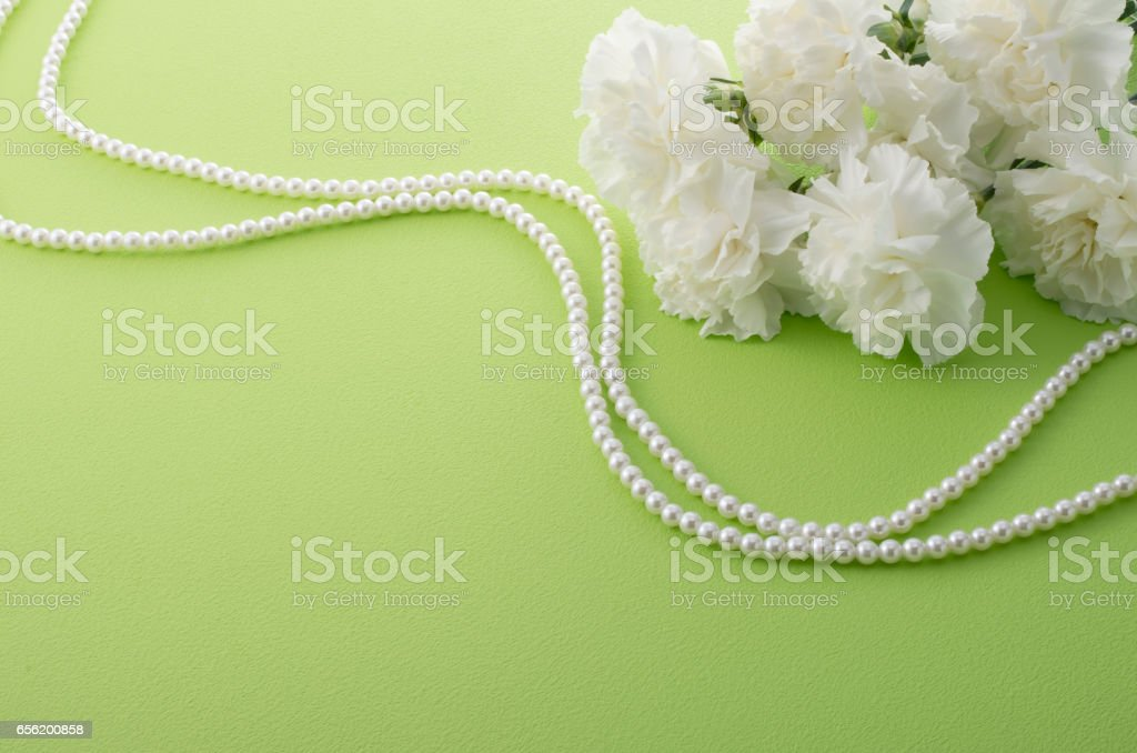 white carnation and pearl necklace stock photo