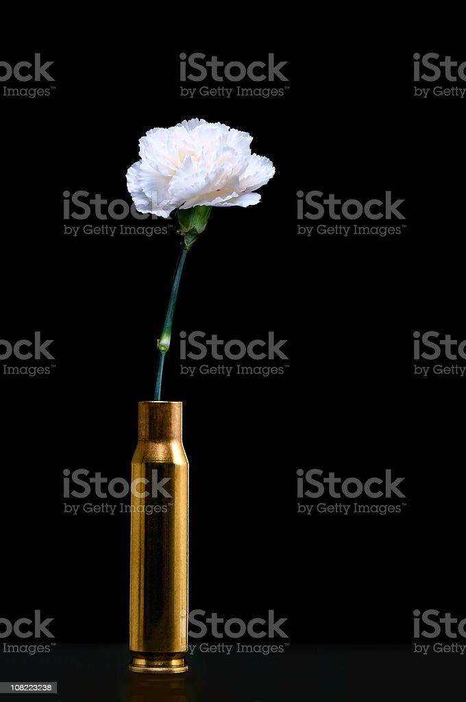 White Carnation inside ammunition shell - Peace symbols stock photo