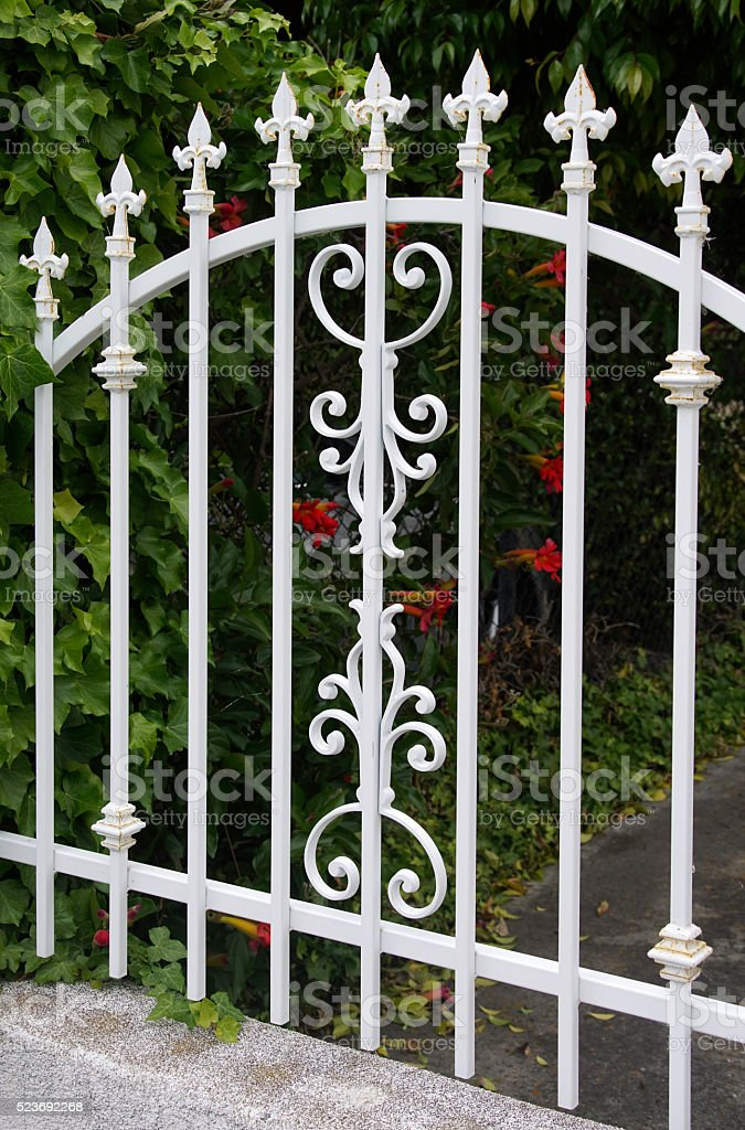 White cast iron fence guards grounds of a fancy home stock photo