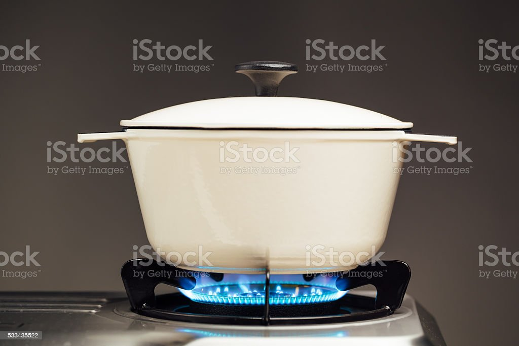 white cast iron saucepan on the gas stove stock photo