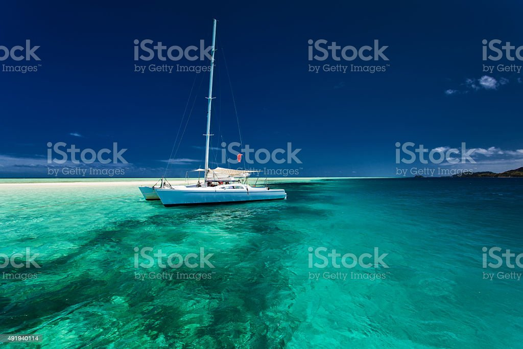 White catamaran in shallow tropical water with snorkeling reef stock photo