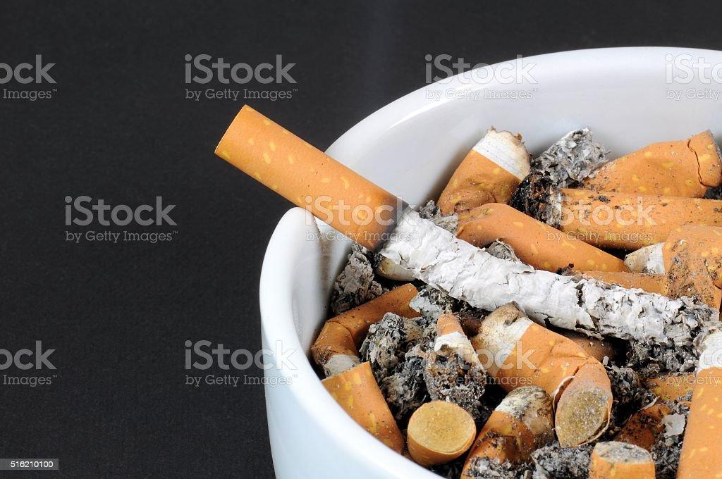 White ceramic ashtray detail full of smokes cigarettes stock photo