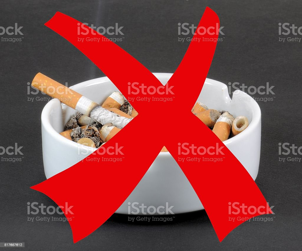 White ceramic ashtray full smokes cigarettes with red prohibition sign. stock photo