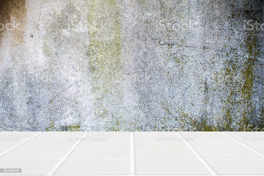 white ceramic mosaic floor and moss concrete wall stock photo