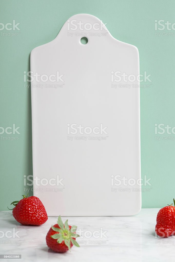 White ceramic serving board and berry over light blue background stock photo