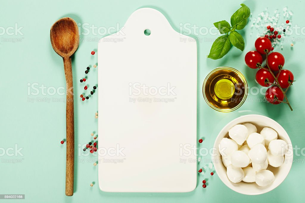 White ceramic serving board and salad ingredients over light blu stock photo