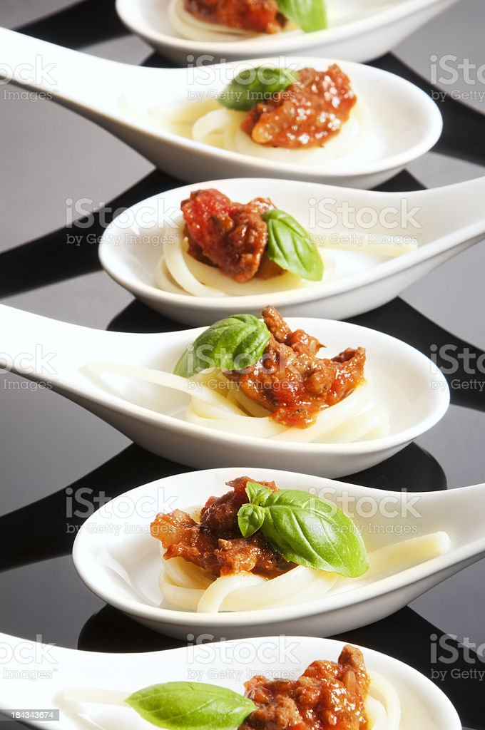 White ceramic spoon canapés in a line on black background stock photo
