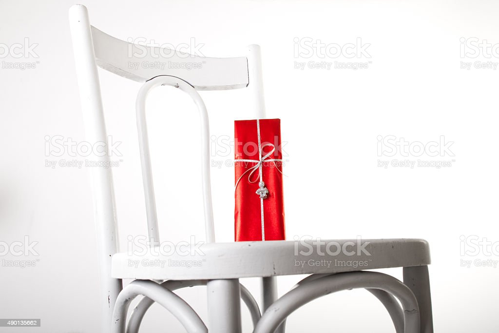 White chair with red gift and silver angel ribbon royalty-free stock photo