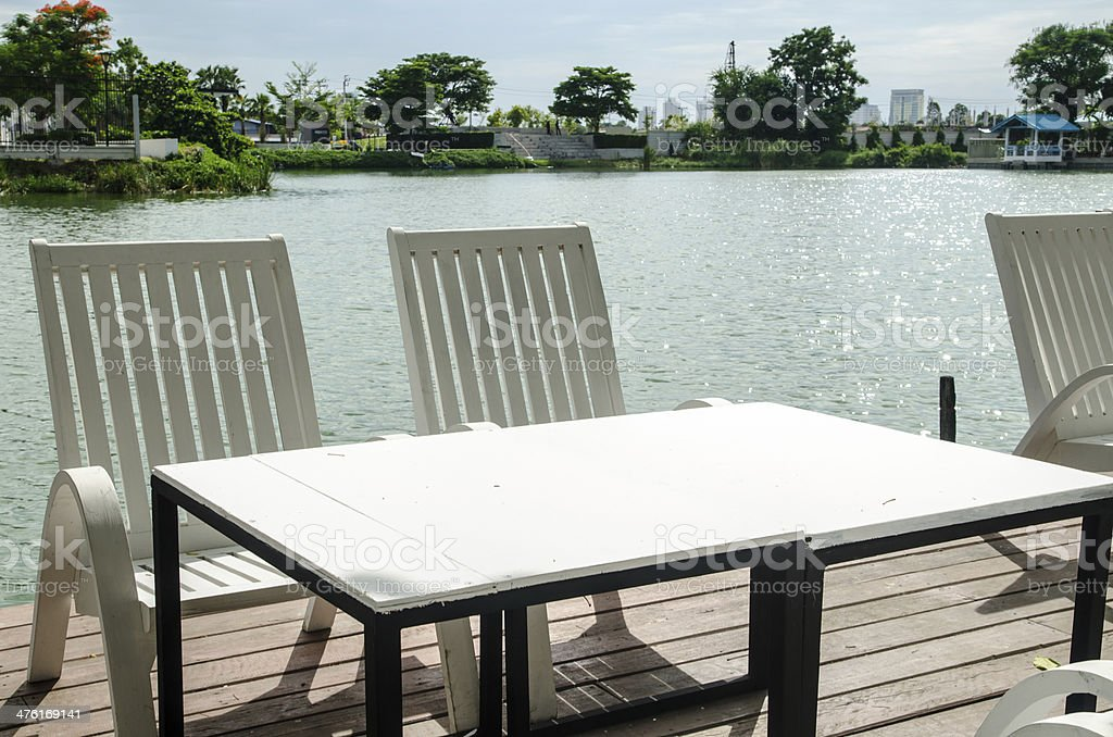 white chairs and table on coast of a reservoir royalty-free stock photo
