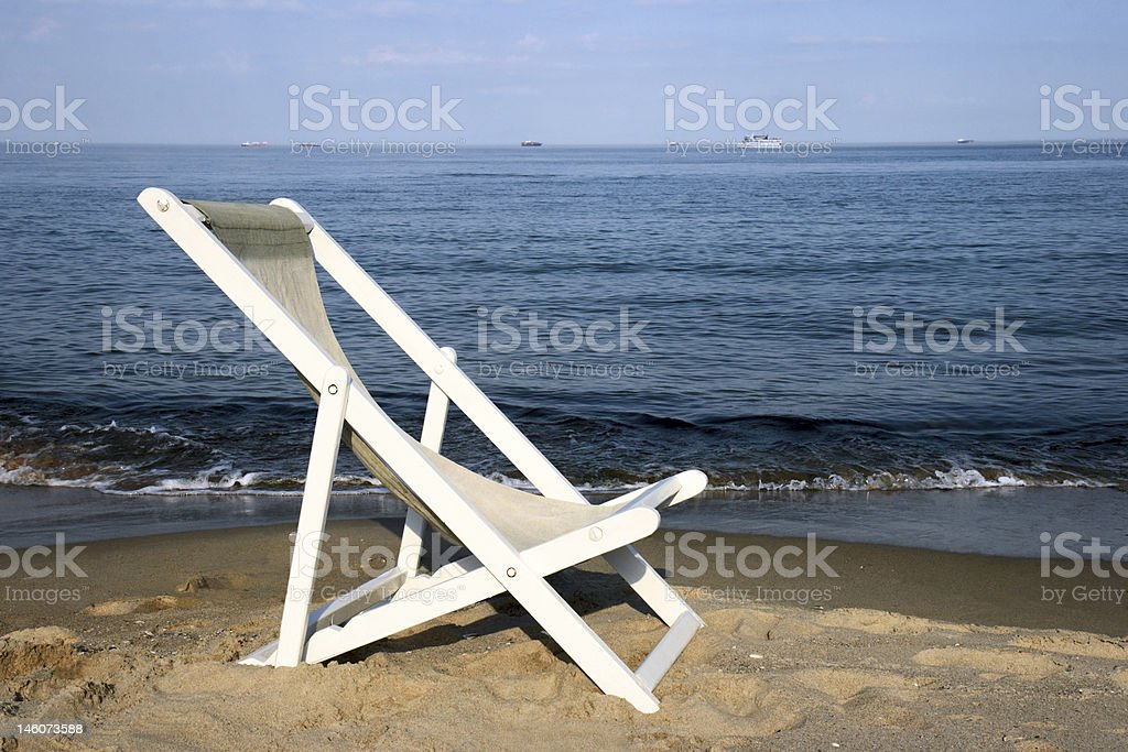 White chaise lounge on a beach royalty-free stock photo