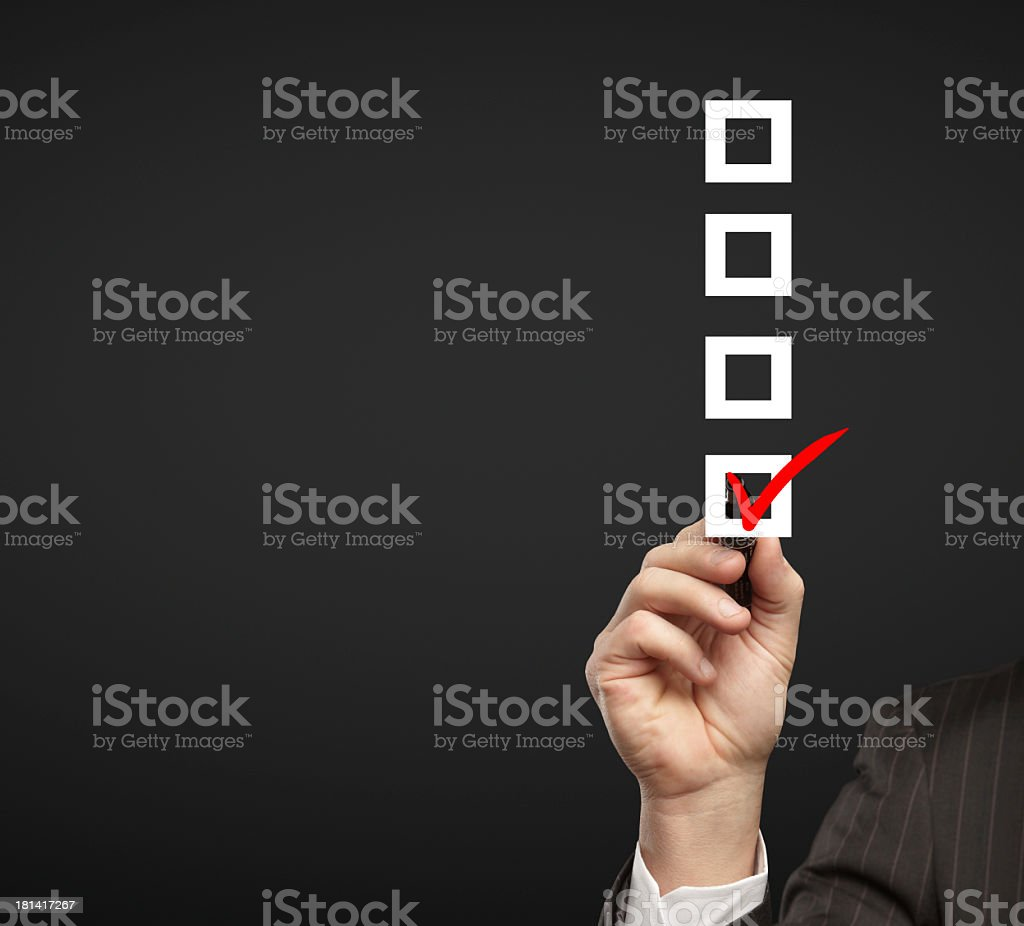 4 white checkboxes with a man checking one of the boxes stock photo