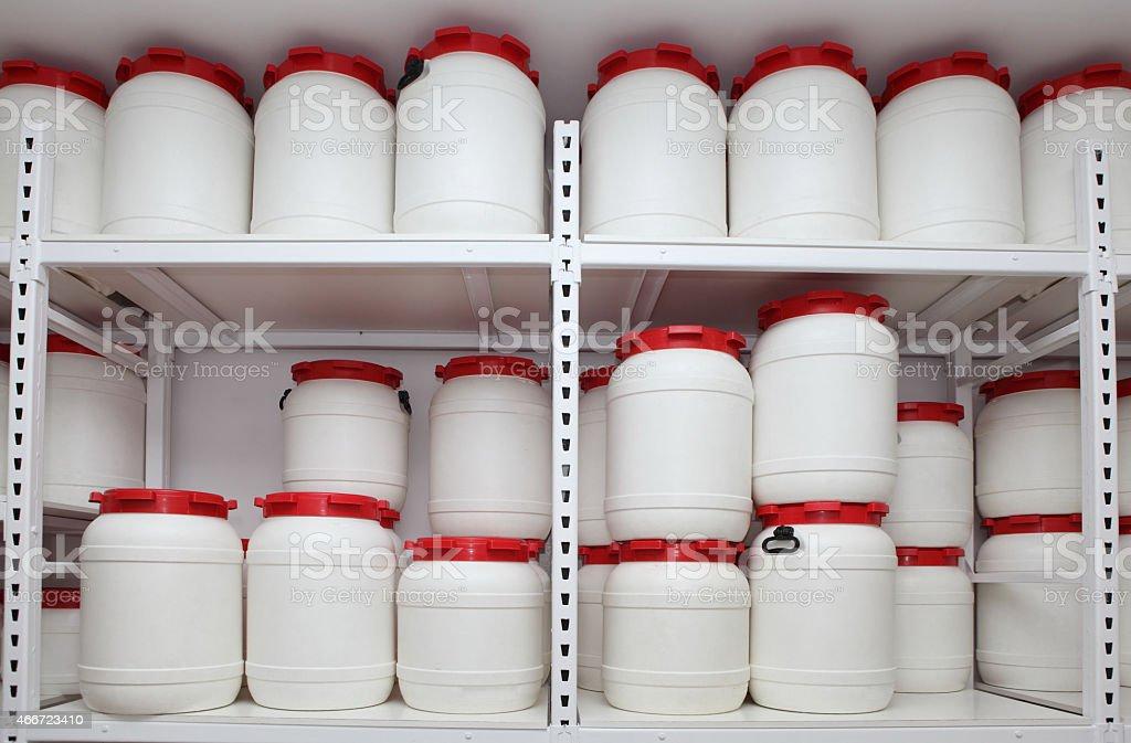 white chemical plastic barrels on shelves in storehouse stock photo