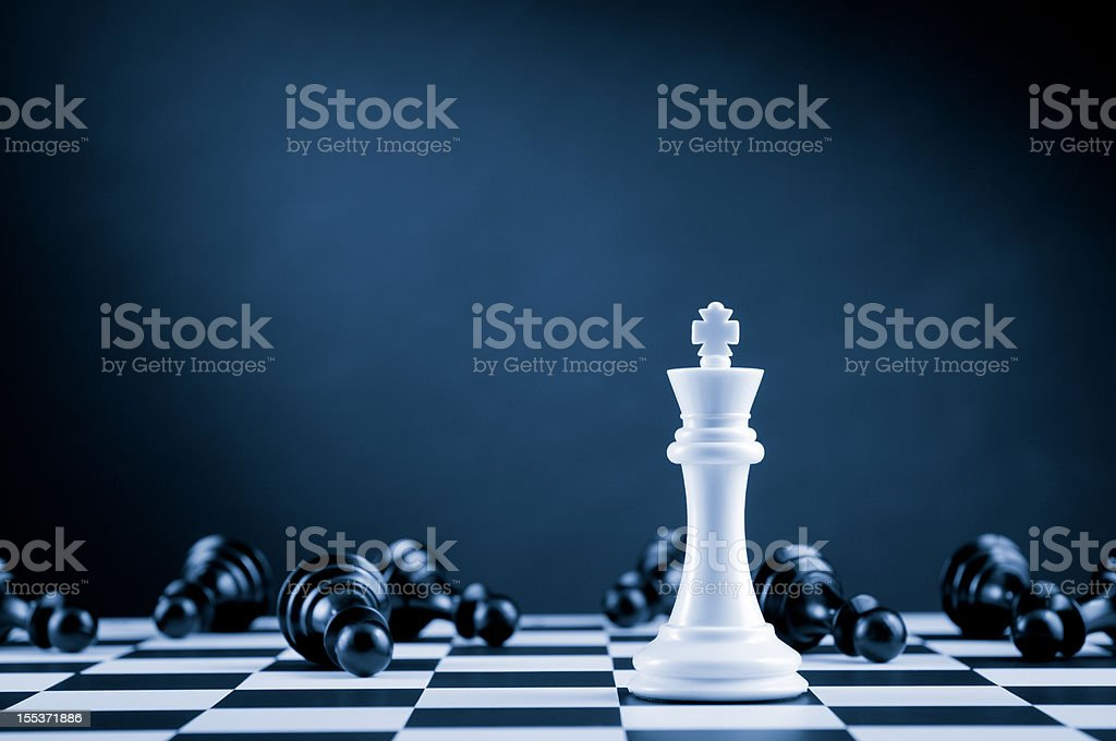 White Chess King among lying down black pawns on chessboard stock photo