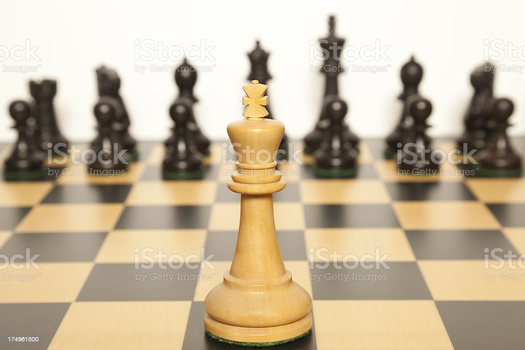 White chess king faces black opponents stock photo