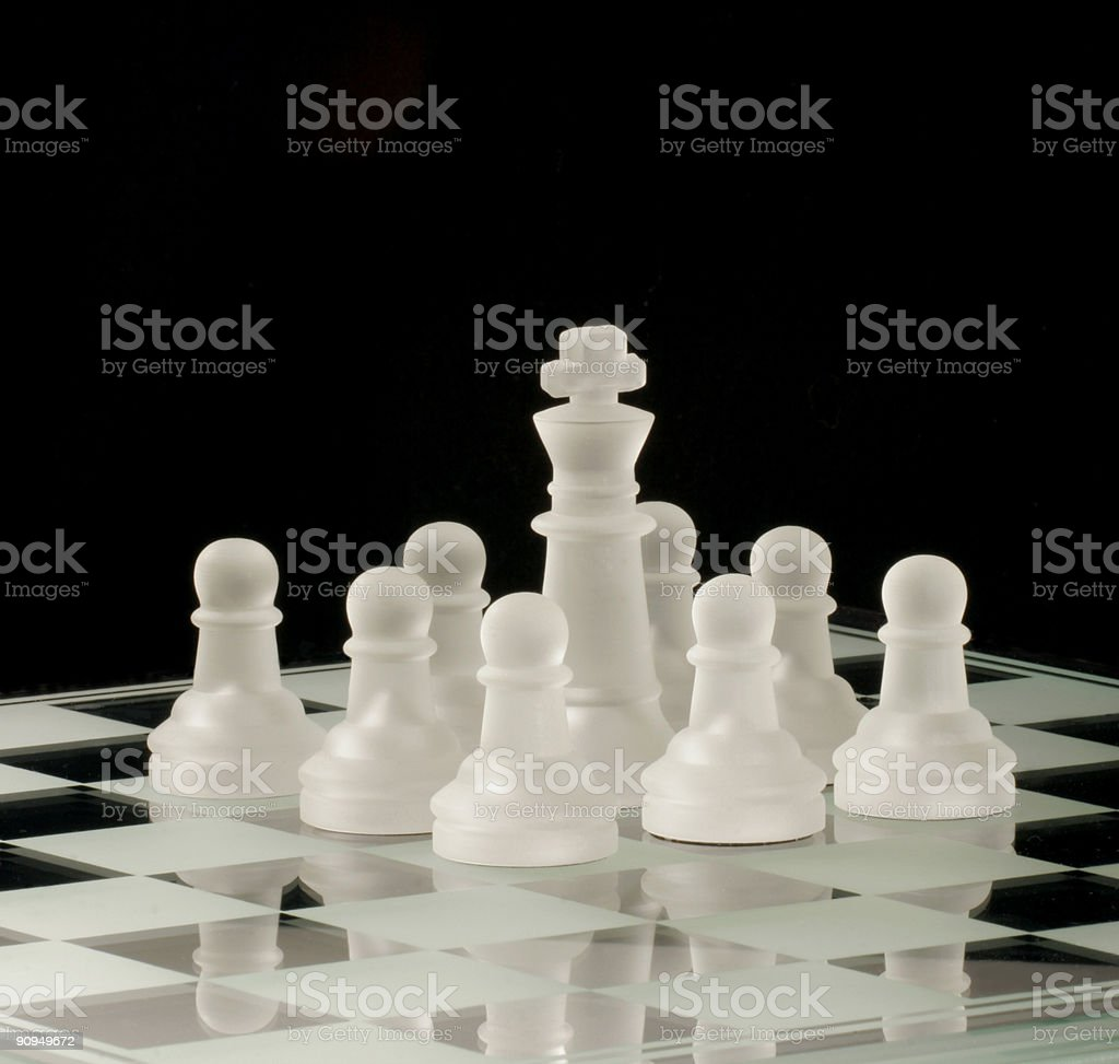 White chess king surrounded by pawns stock photo