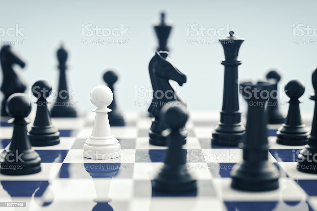 White Chess Pawn Surrounded By Black Chess Pieces stock photo