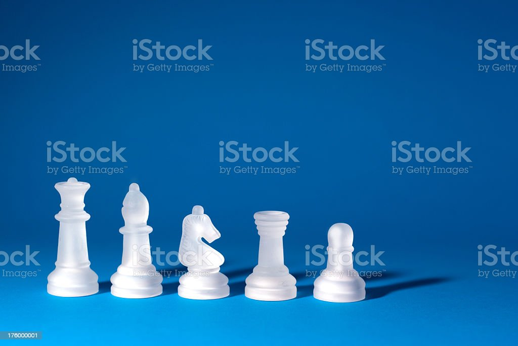 White Chess Pieces on Blue royalty-free stock photo