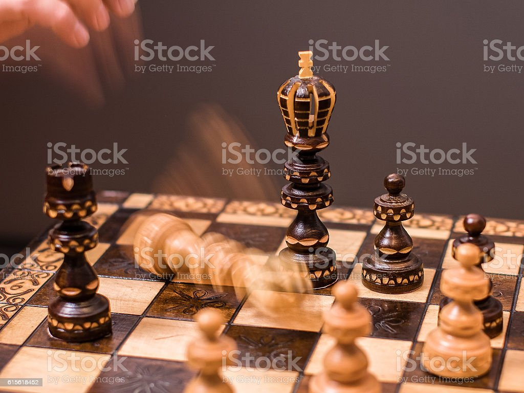 White chess player gives up; King falling after checkmate stock photo