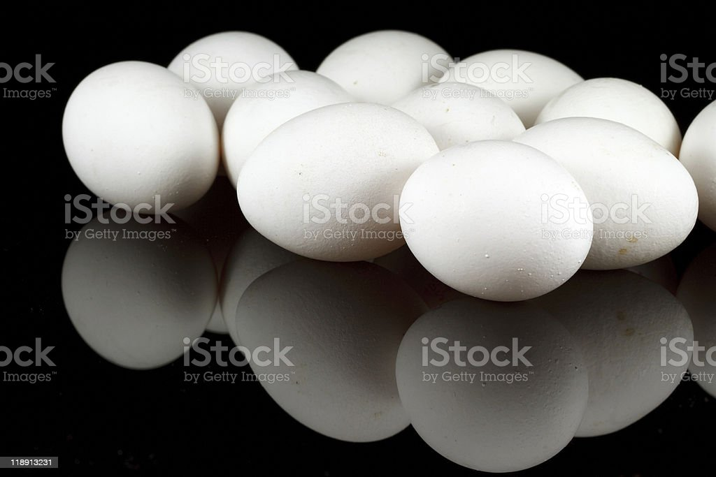 White chicken eggs on reflecting black background royalty-free stock photo