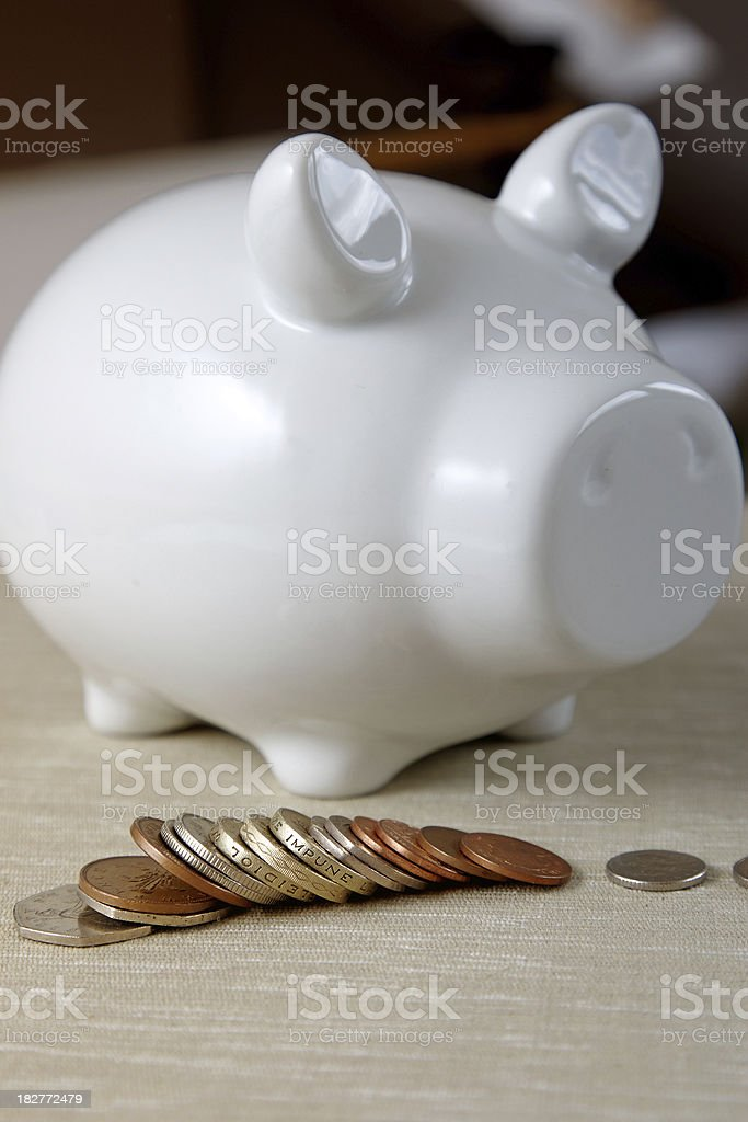 White china piggybank with UK coinage royalty-free stock photo