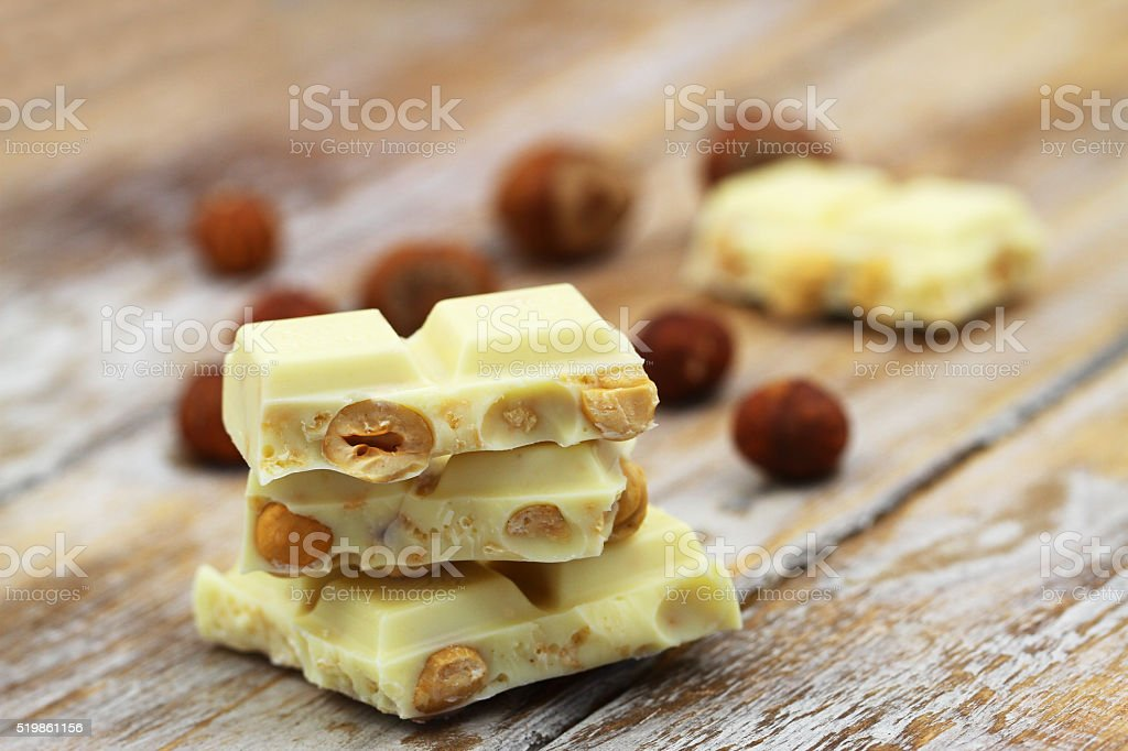 White chocolate with hazelnuts stacked up on rustic wooden surface stock photo