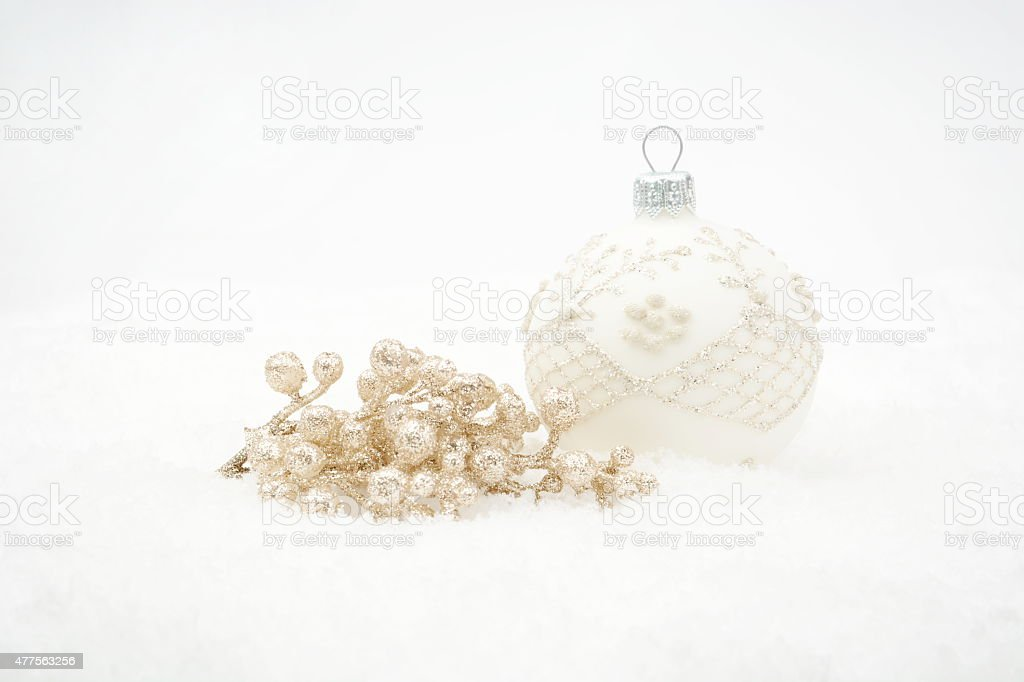 White christmas bauble with gold decoration on snow stock photo