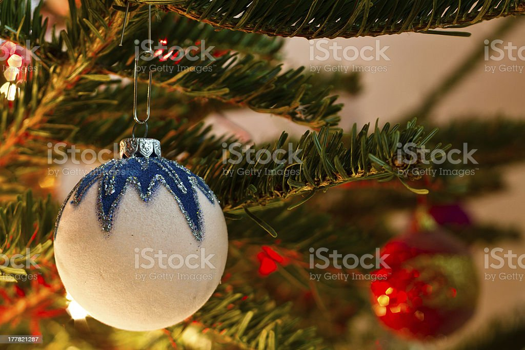 White Christmas globe hanging from a branch of pine royalty-free stock photo