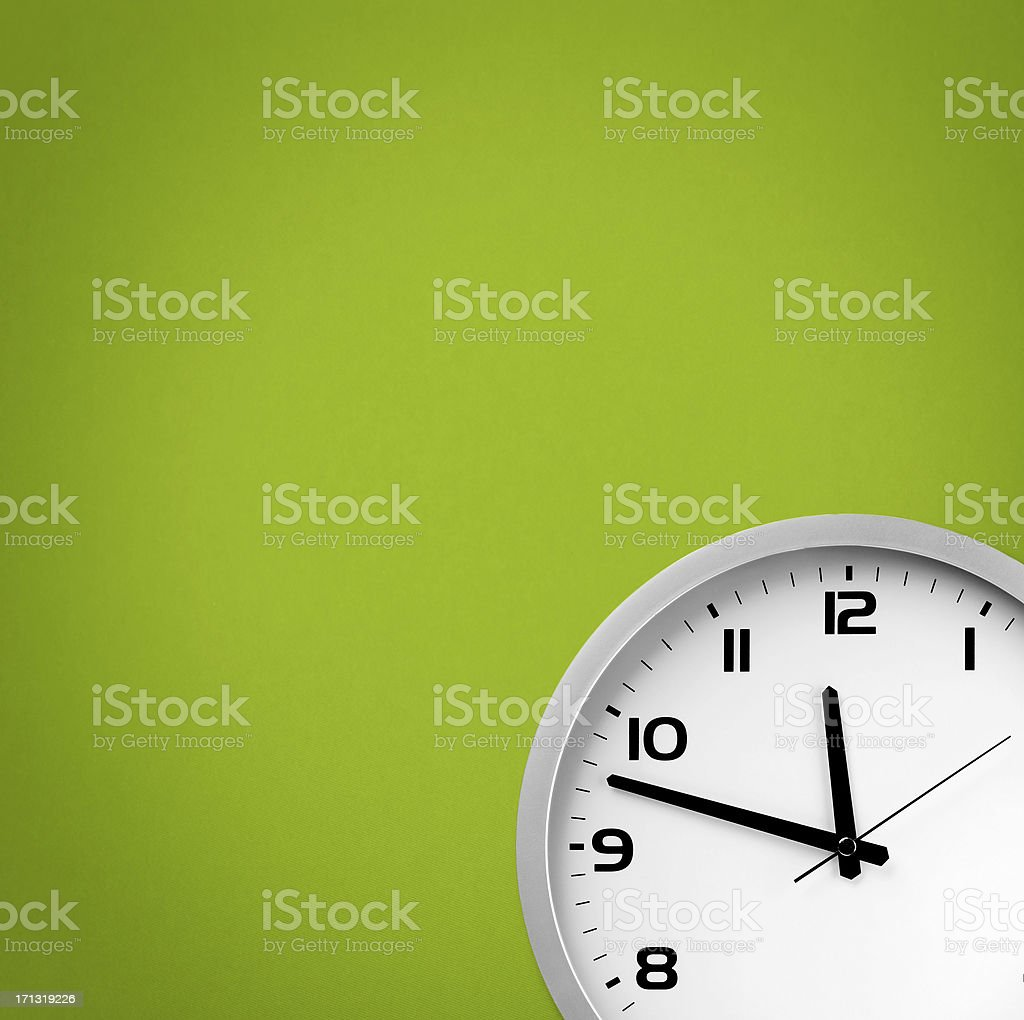 White clock on a green background stock photo