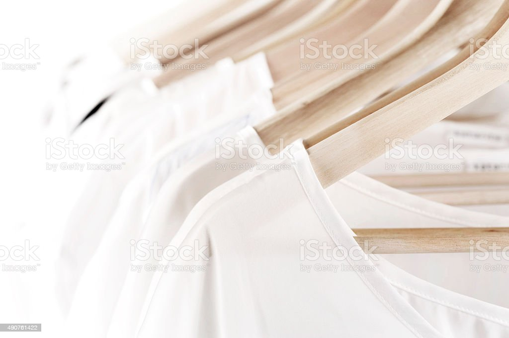 White clothes on hangers stock photo