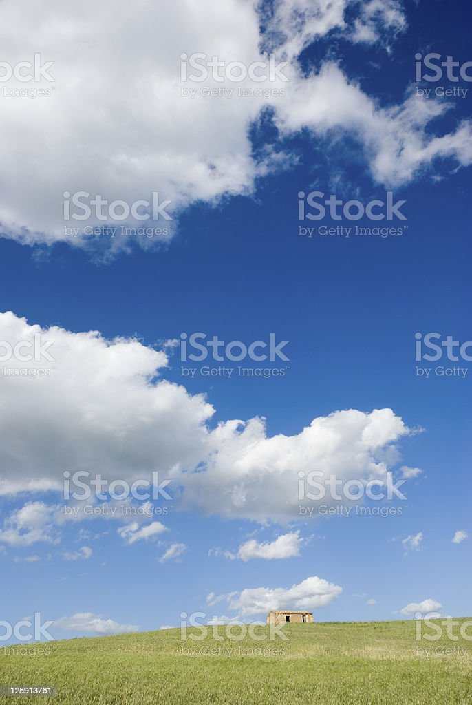 white clouds above a farm on the hill royalty-free stock photo