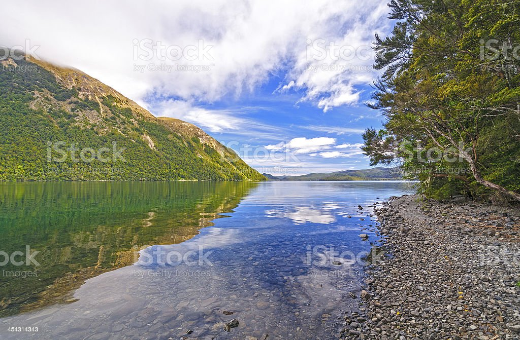 White Clouds and Blue Sky over an Alpine Lake stock photo