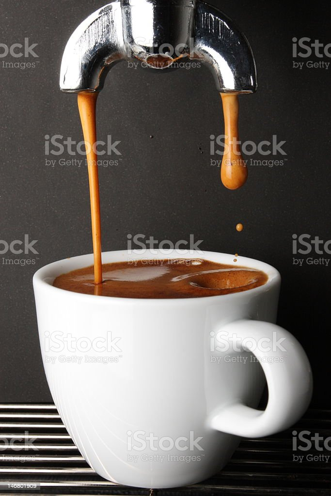 White coffee cup as it is filled with espresso stock photo