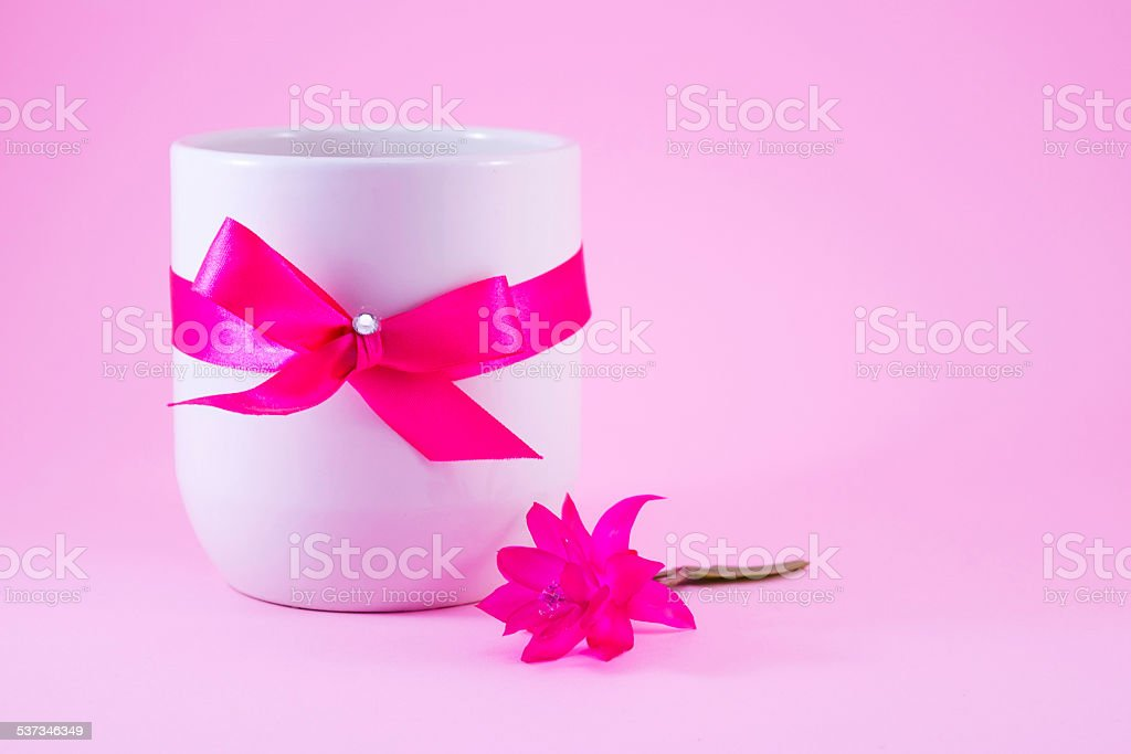 White coffee mug decorated with a pink ribbon royalty-free stock photo