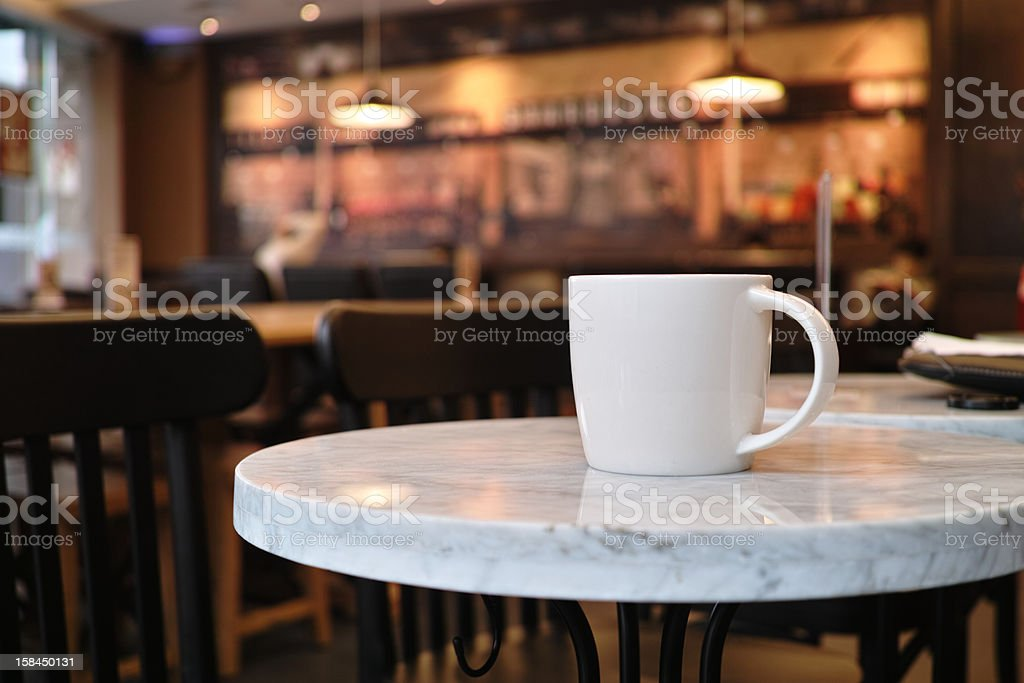 White coffee mug sitting isolated in a cafe stock photo