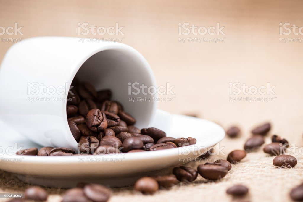 White coffeecup with coffeebeans on gunny background stock photo