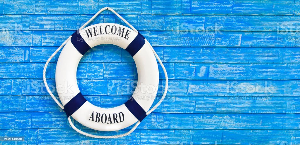 White color Life buoyancy with welcome aboard on it hanging on blue wall. stock photo