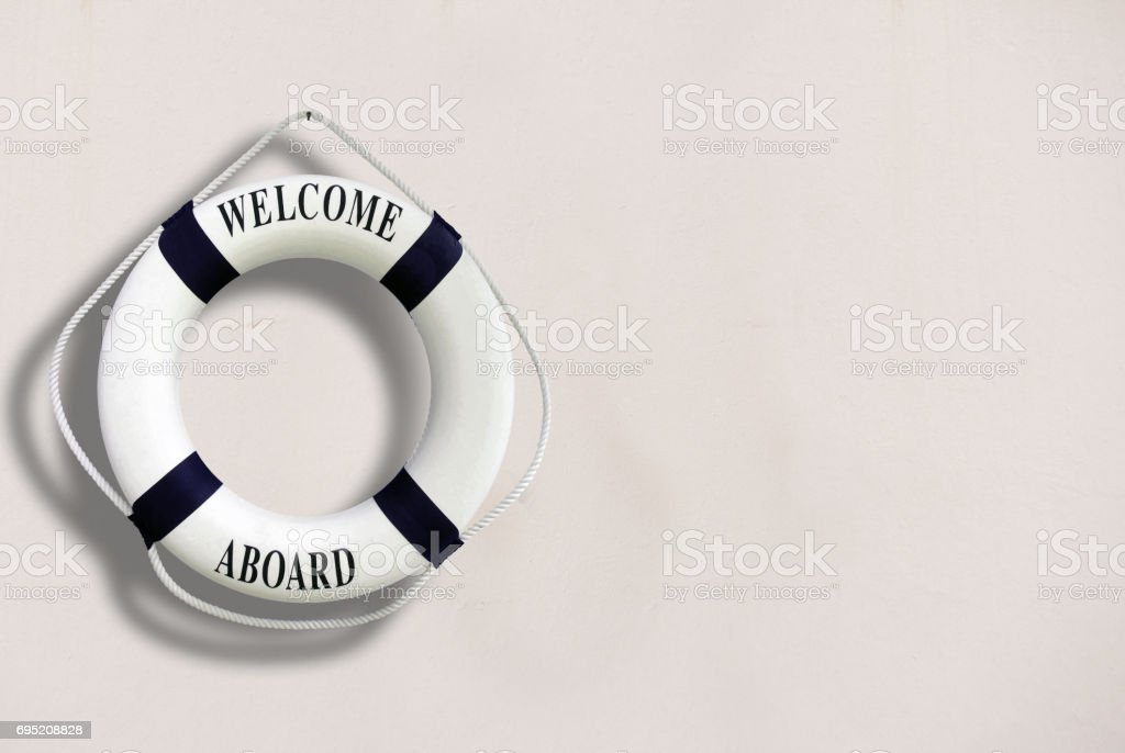 White color Life buoyancy with welcome aboard on it hanging on white concrete wall. stock photo