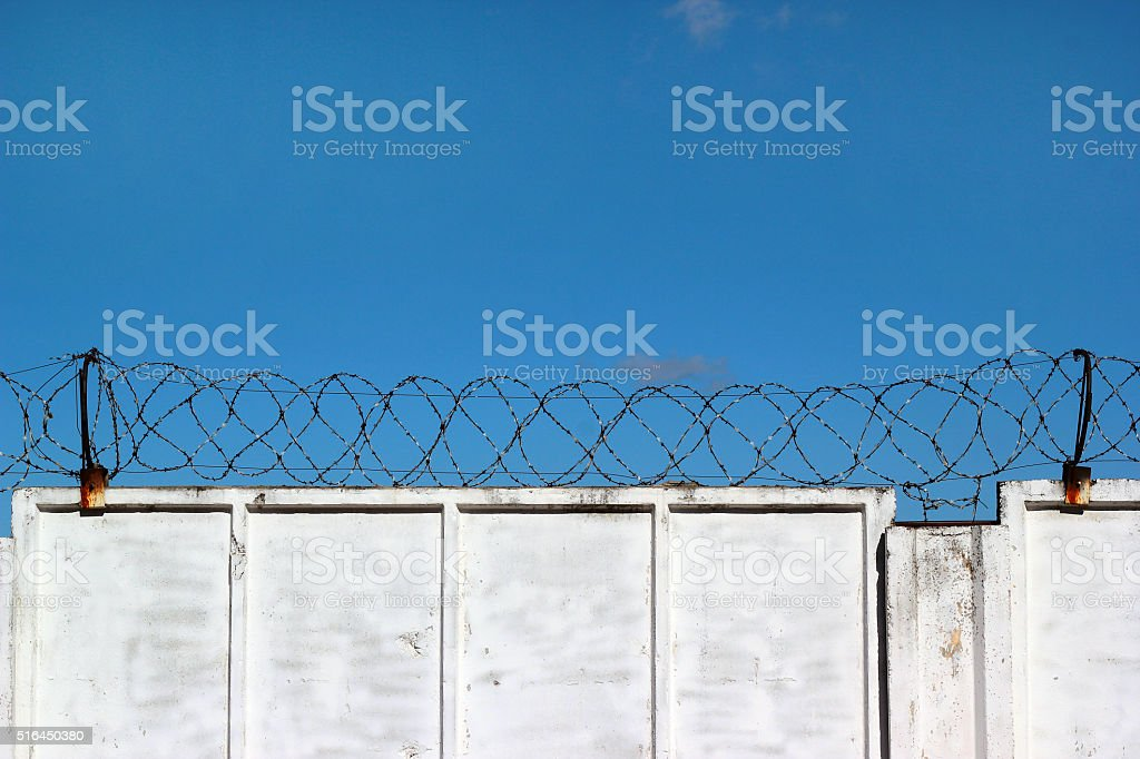 White concrete fence with barbed wire against a blue sky stock photo