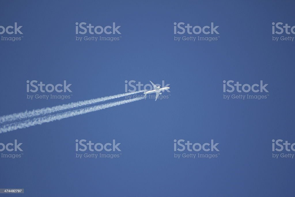 White Condensation Trail of an Aircraft in the Blue Sky stock photo