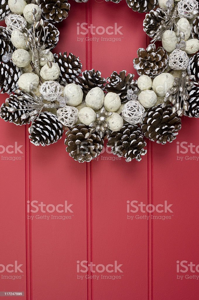 White cone wreath on red paneled wall royalty-free stock photo