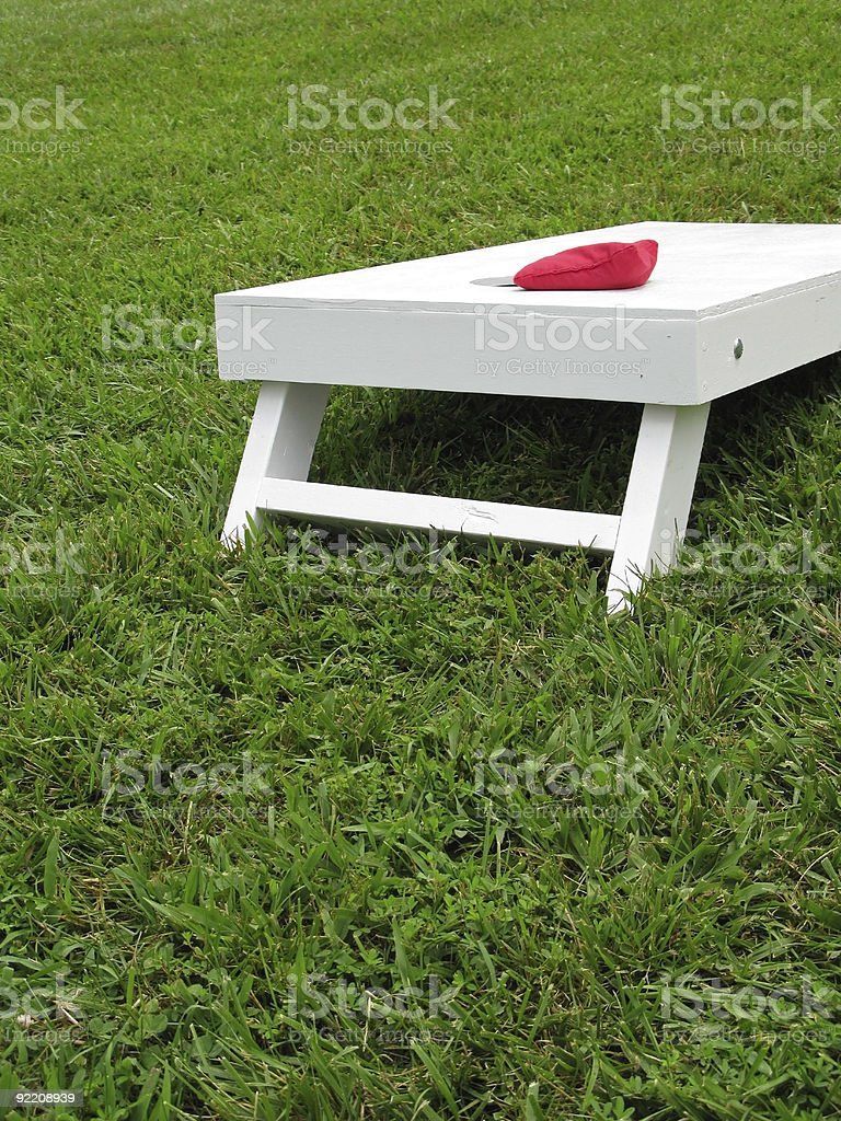 White Cornhole Board with Red Bag Near the Hole stock photo