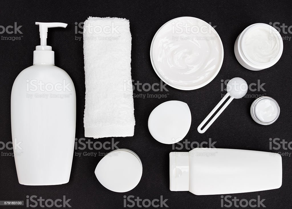 White cosmetic containers on black surface stock photo