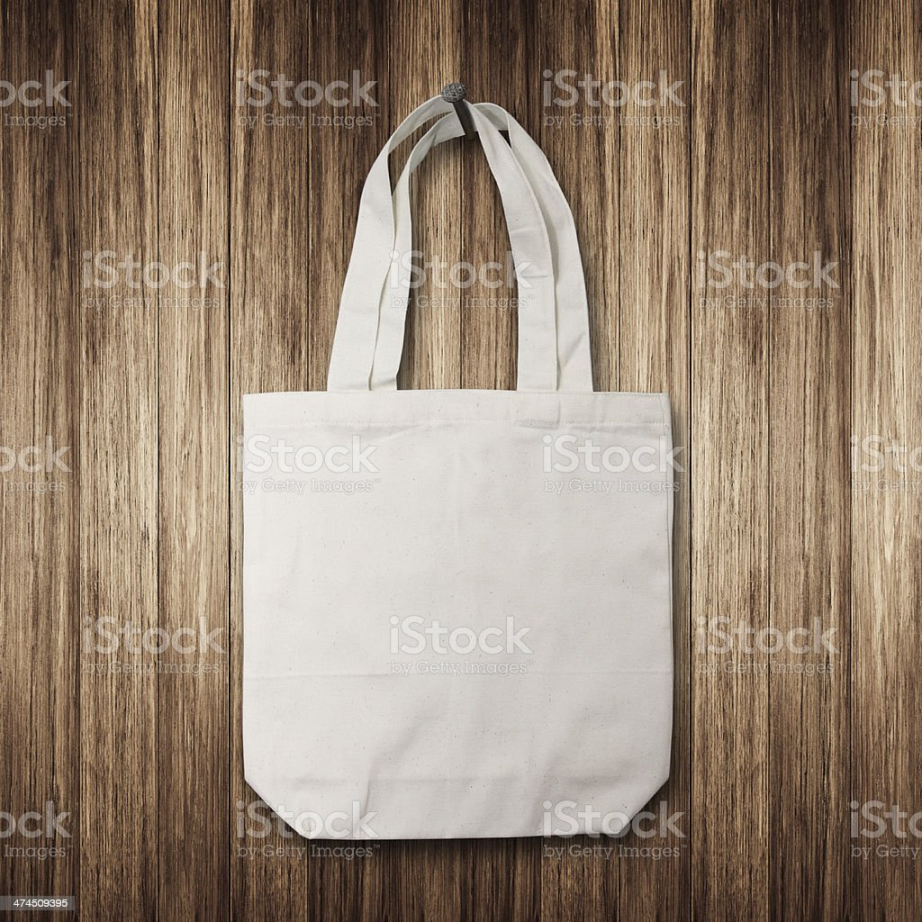 White cotton bag hanging on a wooden wall stock photo