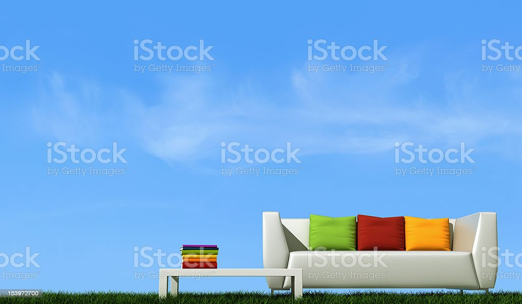 White couch with colorful pillows and matching table outside stock photo