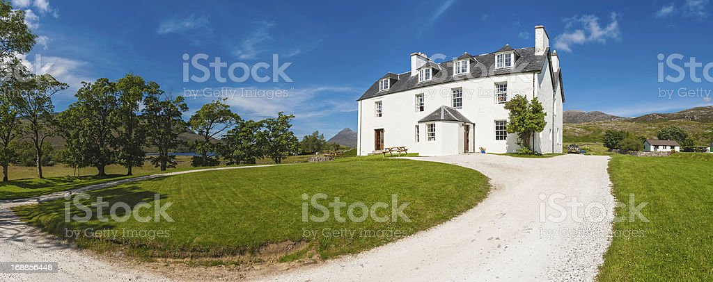 White country house with green lawn in picturesque rural location stock photo