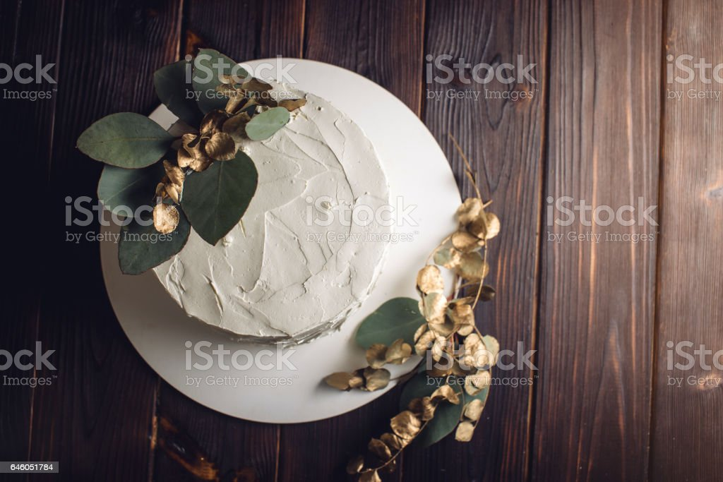 white cream cake decorated with a branch with gold leaves stock photo