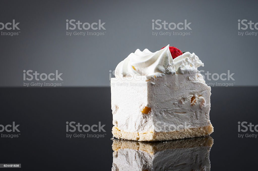 White cream cake with strawberry on reflective table stock photo