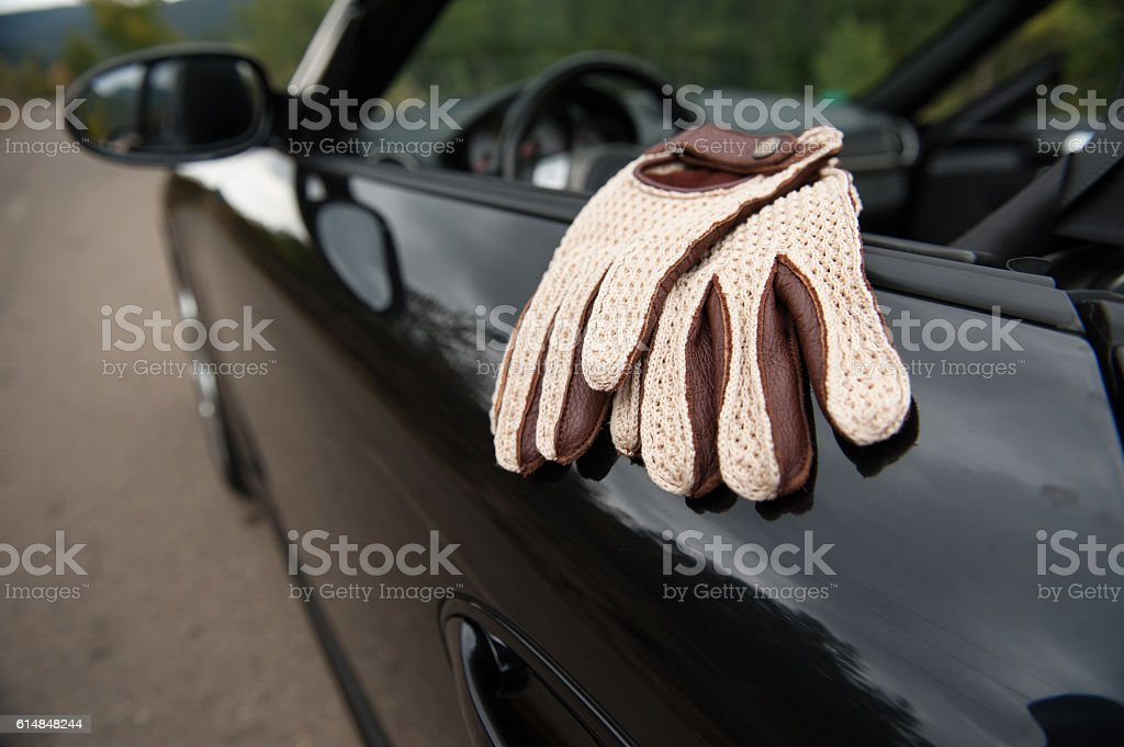 White crochet driving gloves - convertible sports car stock photo